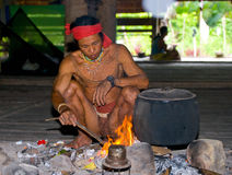 Man Mentawai tribe sitting by the fire in the house. Royalty Free Stock Photo