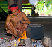 Man Mentawai tribe sitting by the fire in the house. Royalty Free Stock Image