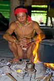 Man Mentawai tribe sitting by the fire in the house. Stock Images