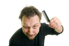 Man with messy hair. Holding a comb Royalty Free Stock Photography