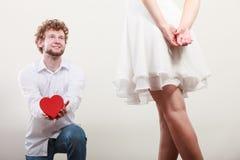 Man met hart gevormde giftdoos voor vrouw Royalty-vrije Stock Foto's