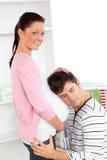 Man met hoofd op de buik van zijn zwangere vrouw Royalty-vrije Stock Foto's