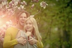 Man met meisje of mooie vrouw bij tot bloei komende magnolia stock fotografie