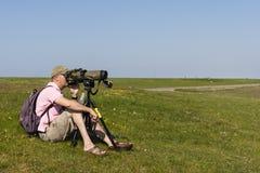 Vogelaar, Birder. Man met telescoop op Schiermonnikoog; Men with telescope at Schiermonnikoog stock photography