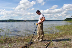 Man with metal detector. On a lakeshore in wicklow ireland stock photography
