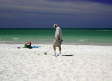 Man with metal detector. Man using metal detector on beach with green ocean and blue sky in background royalty free stock photography