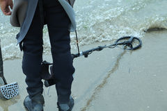 Man with metal detector on the beach to find lost objects Royalty Free Stock Photography