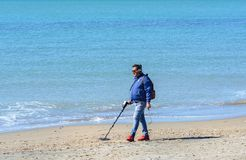 A man with a metal detector is looking for expensive jewelry lost in the sea. A man walks along the beach in search of jewels stock photography