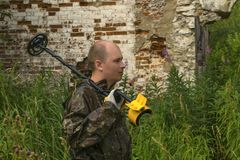 A man with a metal detector. Man in camouflage with a metal detector on his shoulder against the background of overgrown ruins of building stock image
