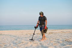 Man with a metal detector on a sea sandy beach.  stock image