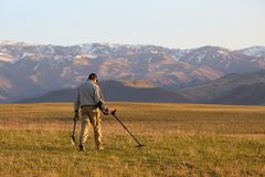 A man with a metal detector in search of a treasure stock images