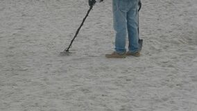 A man with a metal detector and a shovel on the beach.