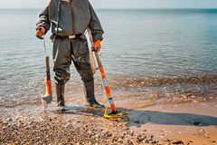 A man with a metal detector stands on the beach, ready for new archaeological finds. Sea on the background royalty free stock images