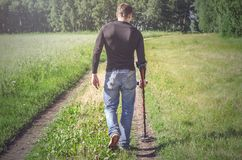 Metal detector. Coin search. Man with metal detector walking on old country road and searching for ancient relics stock images
