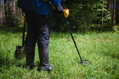 A man with a metal detector in the woods stock image