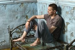 Man on the metal rusty bed Royalty Free Stock Image