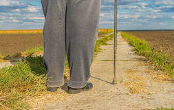 Man with metal walking stick standing on a concrete road. Among agricultural fields at fall season (shoot from behind Stock Photography