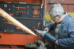 Man in metal workshop. A senior metalworker  with an electric drill working on a piece of metal in his workshop Royalty Free Stock Photos