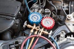 Manômetro que está sendo usado para calibrar a pressão do condicionamento de ar no automóvel Fotos de Stock Royalty Free