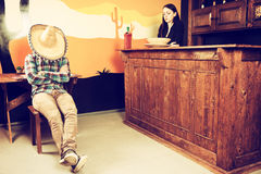A man in a Mexican bar got drunk and fell asleep sitting on a ch. A men in a Mexican bar got drunk and fell asleep sitting on a chair and covered his face with a stock image