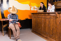 A man in a Mexican bar got drunk and fell asleep sitting on a ch. A men in a Mexican bar got drunk and fell asleep sitting on a chair and covered his face with a stock images
