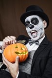 Man with mexican calaveras makeup and carved pumpkin Stock Photography