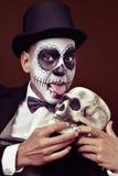 Man with mexican calaveras makeup licks a skull Royalty Free Stock Photography