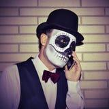 Man with mexican calaveras makeup, on the phone Stock Photos