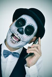 Man with mexican calaveras makeup, on the phone Stock Photography