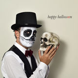Man with mexican calaveras makeup and skull, and text happy hall Royalty Free Stock Photo