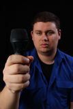 Man with Mic Left. Man in a blue shirt holidng a microphone Stock Photography