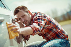 Man with a microfiber wipe the car polishing stock image