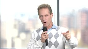 A man with a microphone refers to the audience. Male person with microphone indicating with index finger forward. Public speaking concept stock video