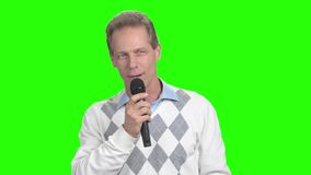Man with a microphone speaking to the audience. Mature man with microphone having discussion with public and gesturing, green screen. Man speaking at stock video footage