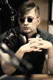 Man with microphone in studio. Man wearing dark sunglasses with microphone and headphones in studio Stock Photography