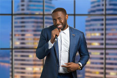 Man with microphone on urban background. Evening live perfomance. Afro american professional jazz singer Stock Photo
