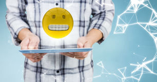 Man mid section with tablet, emoji, flare and network against blue background Royalty Free Stock Photo