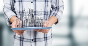Man mid section with tablet and sketch of building against blurry grey room. Digital composite of Man mid section with tablet and sketch of building against Stock Images