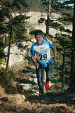 Man, middle-aged runner runs distance of race uphill in a pine forest Stock Photos