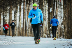 Man middle-aged runner runs on road snowy Park Stock Image