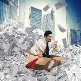 Businessman extricate himself from a sea of paper Stock Photos