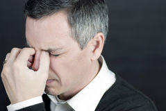 Man With Migraine Holds Bridge Of Nose Royalty Free Stock Photos
