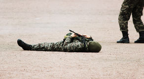 Man in Military camouflage clothing and a mask lying on his back  the sand with  machine guns in  hand during the demonstration pe Royalty Free Stock Photos