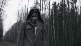 Man in gas mask standing on railway in forest. Stalker, post apocalyptic world