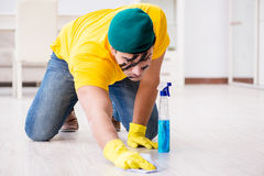 The man in military style cleaning the house Stock Photos