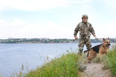 Man in military uniform with German shepherd dog. Near river royalty free stock images