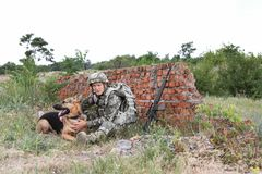Man in military uniform with German shepherd dog. Near broken brick wall Royalty Free Stock Photos