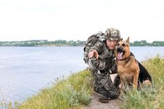 Man in military uniform with German shepherd dog. Near river Stock Image