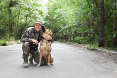 Man in military uniform with German shepherd dog. Outdoors Royalty Free Stock Image