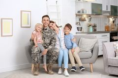 Man in military uniform with his family on sofa stock photos